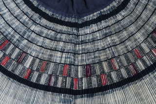 """Pleated skirt, Miao people, China. Cotton, silk. Mid-20th century. 18"""" long by 38.5"""" wide at waistband. Skirt is open at the side, with the pleats joined to a wide cotton waistband. The designs are wax-resist in indigo  ..."""