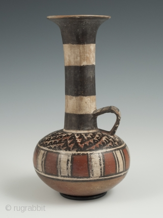 "Small jar, Inca, Peru, Earthenware, 6.5"" (16.5 cm) high, 1470-1550 A.D. An unusual globular terracotta jar with a tall neck, flared top and loop handle, painted on the shoulder with a stylized  ..."
