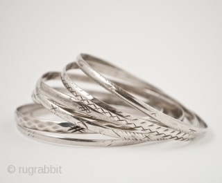 """Schnesshin, seven silver bangles, Tunis, Tunisia. 8"""" (20.2 cm) interior circumference, Mid 20th century. Bangles are worn by Bedouin women in the city of Tunis in groups of seven, which is thought  ..."""