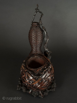 Japanese Bamboo and Wisteria Branch Gourd-shaped Basket  Japanese bamboo and wisteria branch gourd-shaped basket, beautifully woven, with open container for holding floral arrangement at largest node. wisteria branch base.   Circa 1930s   Size: Height  ...