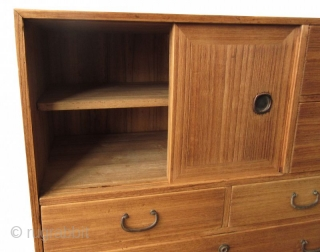 Antique Japanese Kiri Ko Tansu  Japanese small Kiri (paulownia) tansu, with pair of sliding panels concealing a shelved interior compartment, and five drawers of various size with metal pulls and locks. Original condition  ...