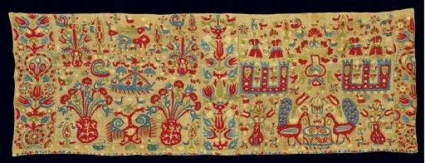 Fragment of an embroidered valance for the adornment of an unknown kind of bridal bed. From Ioannina in Epiros. The diversified scene depicts, in a floral setting, towers and couples, flower vases, peacocks in fountains, and double-headed eagles. 18th c. 1.62x0.57 m. (ΓΕ 6307) image and text copyright Benaki Museum
