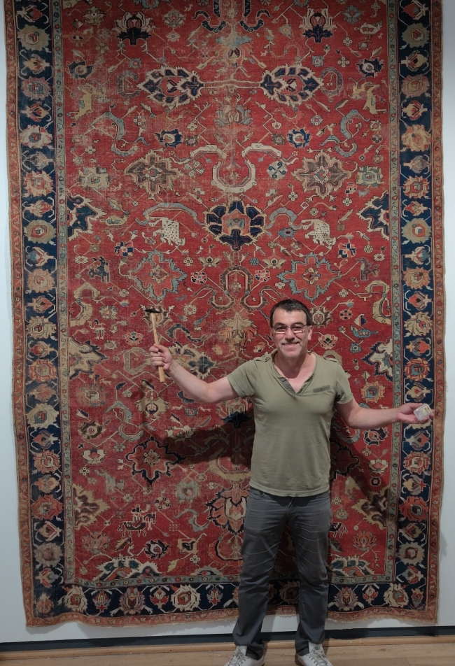 Milani hangs an early Northwest Persian kelleh carpet