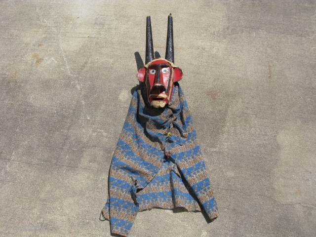 African antelope mask, hand carved wood, red and black paint, metal eyes, blue fabric, the white on the head and around the face and chin is hide tacked on with nails, Bambara  ...