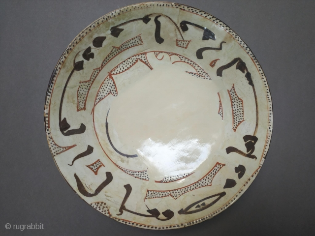 Bowl, of conical form, slip-painted, decorated in manganese and tomato brown under a transparent glaze, with a single band inscription in kufic script below the rim, the words interspersed by irregularly-shaped cartouches  ...