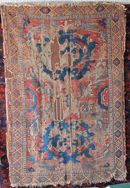 """Smyrna small format carpet, probably 18th century, obvious damage, mounted on brown textile. Big knots, depressed warp, subtle color with two yellows and several blue-greens. (size is 6'3""""x4'1"""")"""