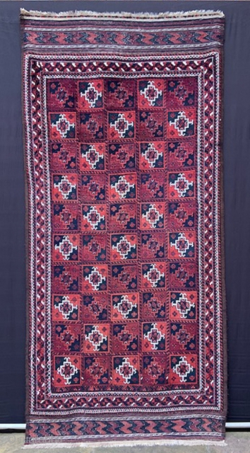 "Baluch rug with overall design of Turkmen 'ayna' guls in full pile with complete plain-weave skirts - 2.44m x 1.17m (8' 0"" x 3' 10"")."
