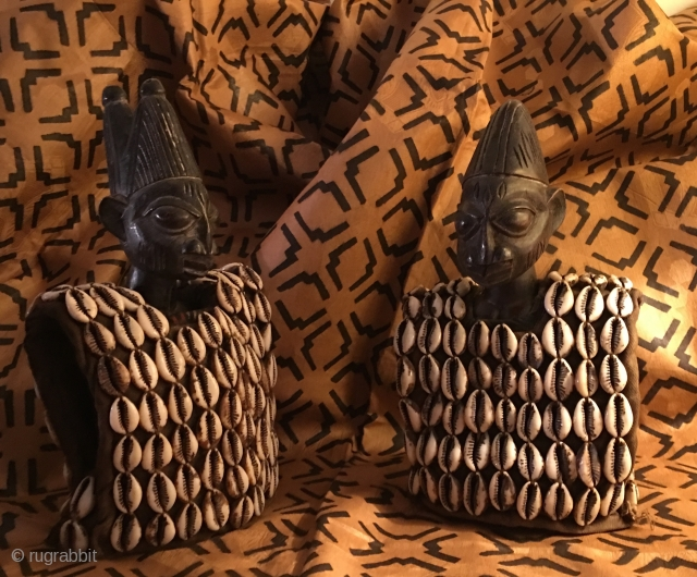 Ibeji, Yoruba sacred twins. Nigeria. Two wooden statues, each 25 cm ca high. Datable 2nd to 3rd q 20th century. Male & female. Both covered in a rich vest with over 130  ...