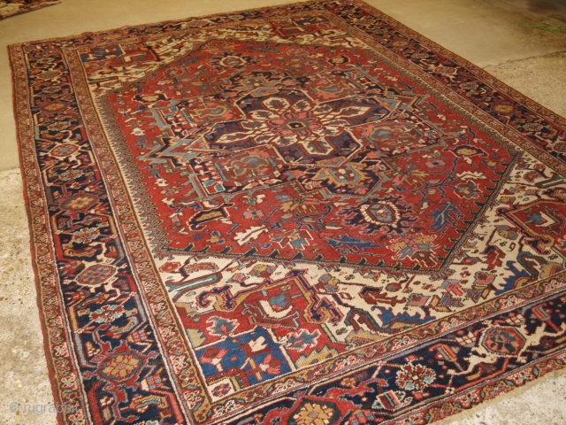 Antique Persian Heriz carpet with a traditional medallion design, soft red field colour with ivory spandrels. Classic dark indigo blue border that is very well drawn. The central medallion in dark indigo  ...