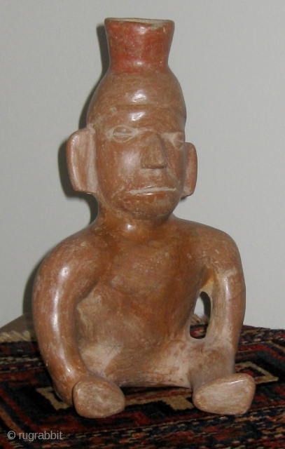 """Pre-Columbian Colima figural vessel in the form of a seated male figure; 300BC to 300AD;  10 1/4"""" high.  Burnished reddish brown terracotta, with a dark fire bloom behind the right  ..."""