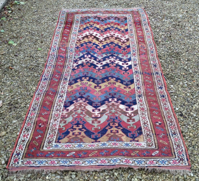 A Northwest Persian rug with a vibrant zig-zag design, probably Kurdish. Some losses and scattered reweaves - see pictures. 19th Century, 260 x 130 cm