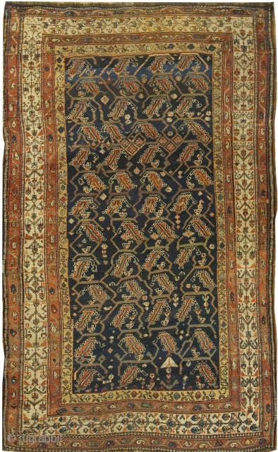 Antique Kurdish Rug circa 1900.An organic leaf design woven in brick  ivory and tan unfolds across the dark Persian blue central field.  A border holding four rows of intricate floral  ...