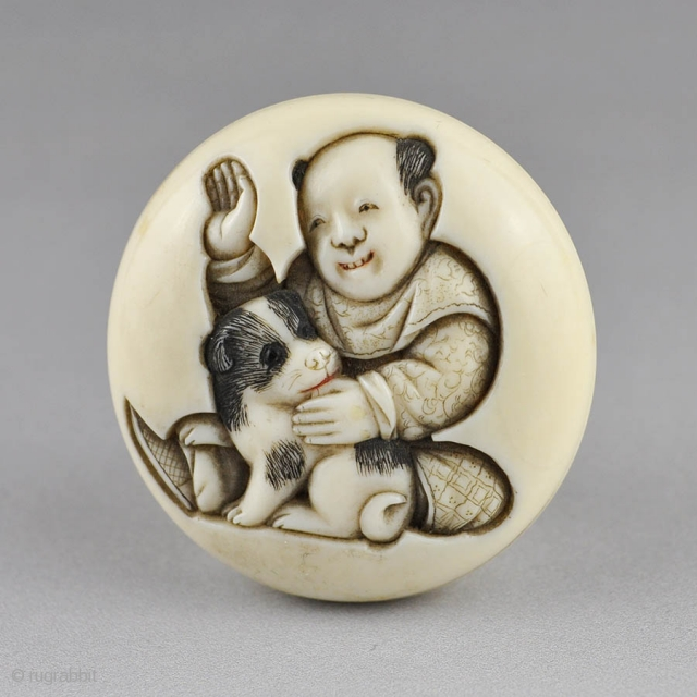 Japanese ivory manju netsuke carved in low relief  with a boy and puppy,  the reverse is carved with another puppy end the carver's signature. The details stained in black and red ink.   ...