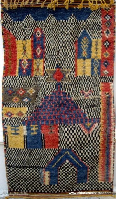 MOROCCAN HIGH ATLAS BERBER RUG. An extraordinary piece, both in design and construction. There are several buildings, probably Mosques and Minarets portrayed in the field. Most unusually, the wool used for the  ...