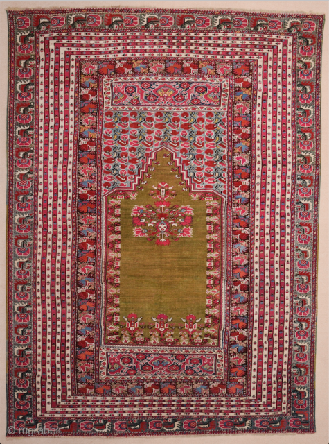 This 19th Century Anatolian Ghordes Green ground prayer rug displays an open field and a steeply towering mihrab shape