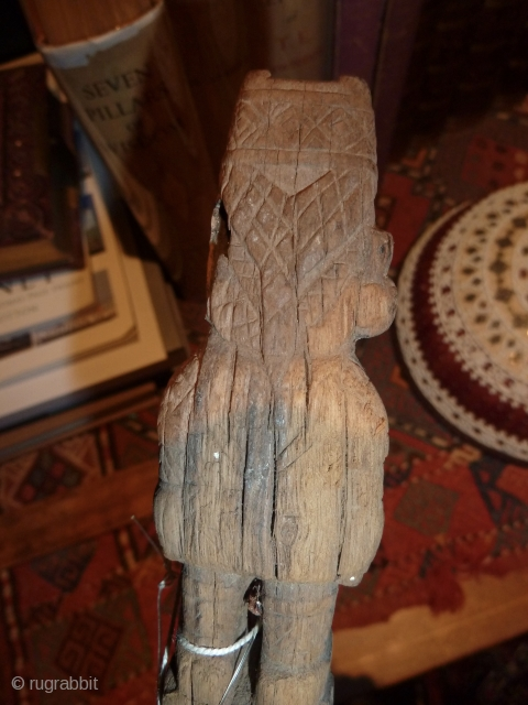 Pre-columbian wooden staff, Wari showing the typical headdress, plaits and costume.