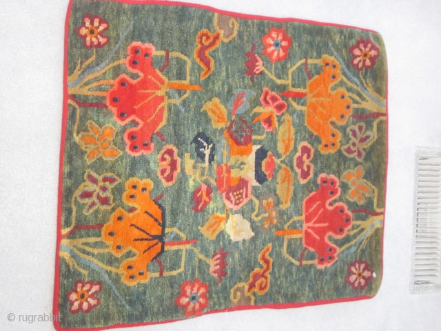 Tibetan mat,23 by30 inches, extravagant floral and cloud band display on abrashed green ground, c.1930
