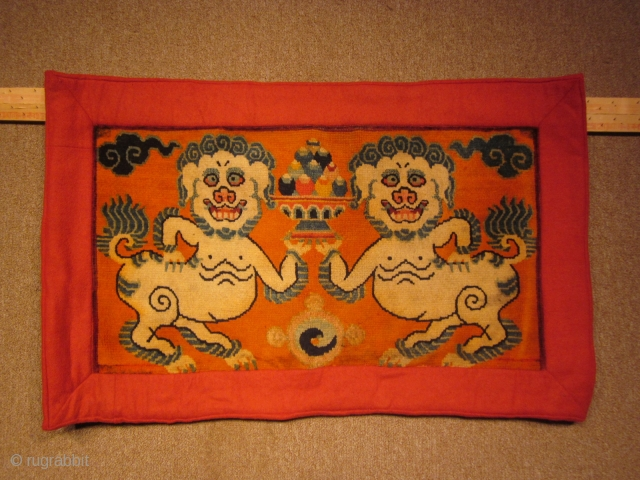 Tibetan mat with two grinning snow lions holding a bowl of flaming pearls, c.1930 SOLD