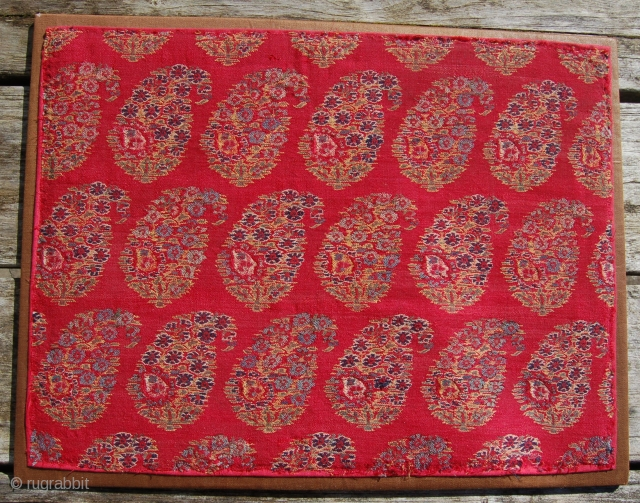 A lovely kashmir shawl fragment with a mother and child boteh design. Early 19th century. Mounted on a wooden board. 45 x 35cm.