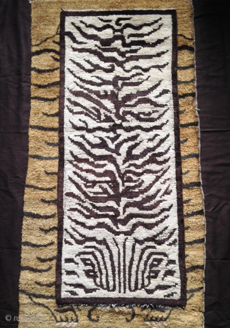 real tiger rug (not fake).. this is a really rare white ground nord west china tiger rug with a fabulous calligraphic drawing.an abstract form of the tiger head is incorporated in the  ...