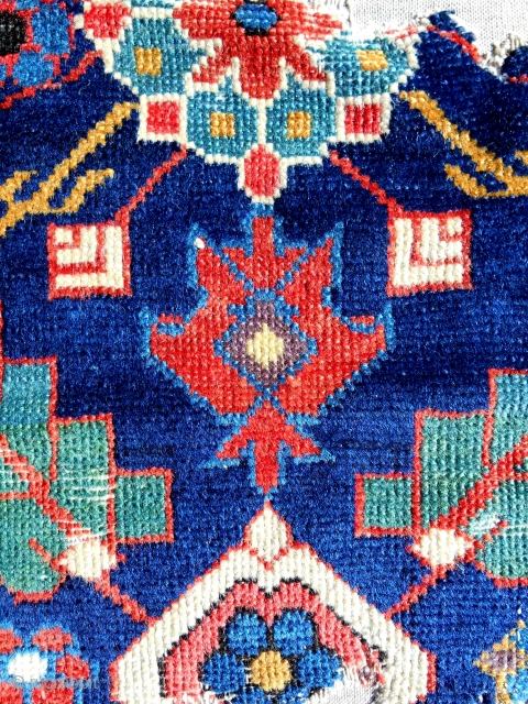 Small Northwest Persian rug fragment. 18th c. Mounted on linen. Crazy color.