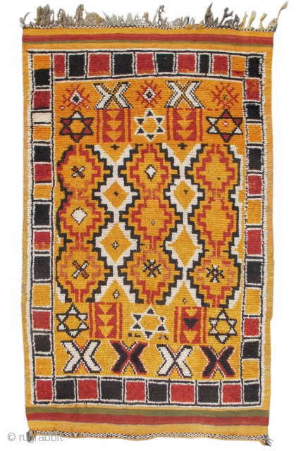 This pleasantly geometric Moroccan rug melds a field design of reciprocal stepped diamonds with a simple border of alternating black and red boxes. Of particular interest are two rows of six-pointed stars,  ...
