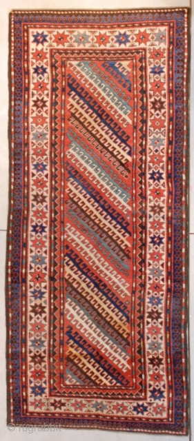 "This circa 1870 Kazak runner measures 3'9"" X 8'8"" (118 x 268 cm). It is a very interesting Kazak. It has diagonal stripes in ivory, green, gold, brown and blue on a  ..."