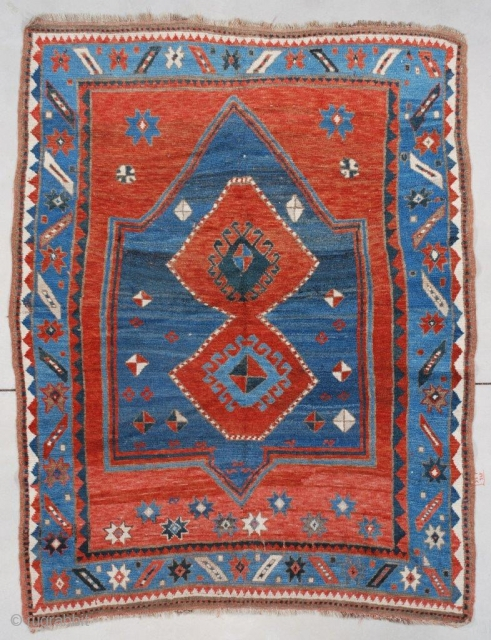 """This circa 1880 Kazak measures 4'3"""" X 6'4"""" (131 x 195 cm). It has a tomato red field with a lovely double niche prayer motif in dark blue containing two tomato red  ..."""