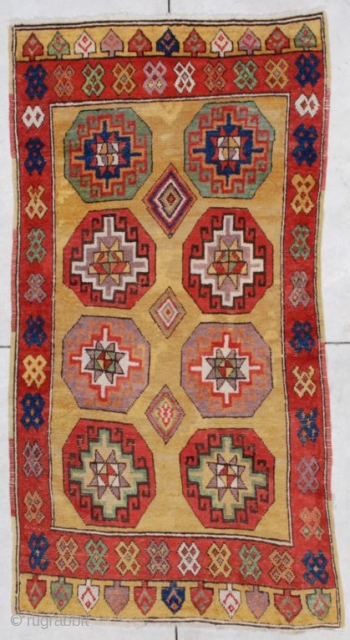 """#6875 Konya  This mid-19th century Konya measures 3'7"""" X 6'8"""". It has a golden butter colored ground with eight octagon shaped medallions in green, red and   aubergine divided by three nicely  ..."""