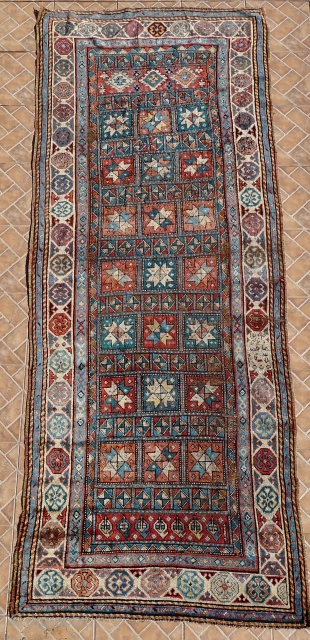 A Genje long rug with star design, late 19 th. century,  Size:  306 x 120 cm. (10ft x 4ft.) Inscribed in the right border and dated 1290 AH/ 1873 AD A few areas  ...