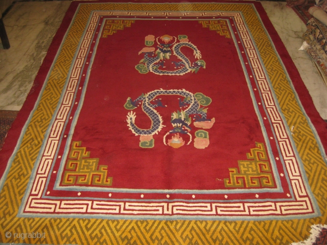 Early 20th century double dragon carpet with borders featuring the repeating swastikas and fretwork, needs repair, measuring 9.5 x 6.5 ft approx.