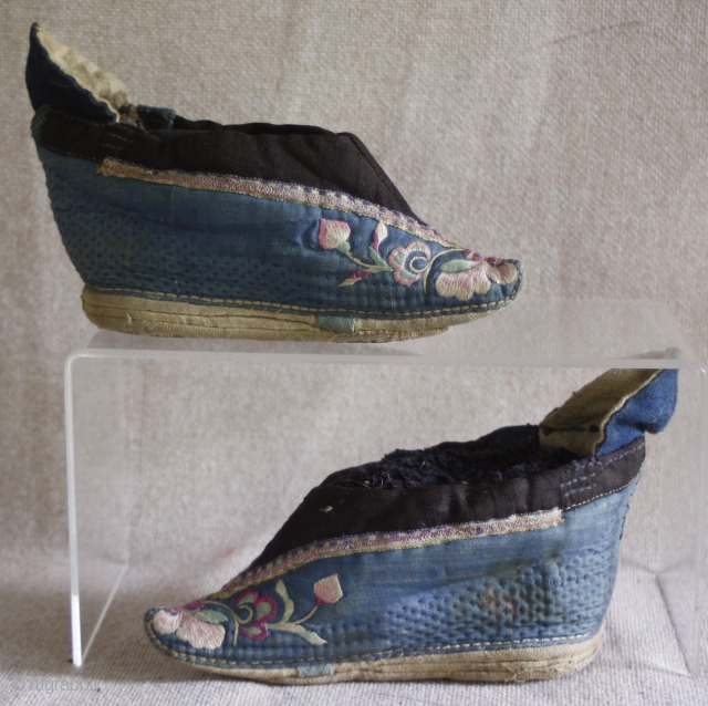 TC 388  This antique Chinese pair of lotus embroidered lotus shoes are most likely from northern china. the vamp is a quilted cotton fabric. Each shoe is embroidered with the same  ...