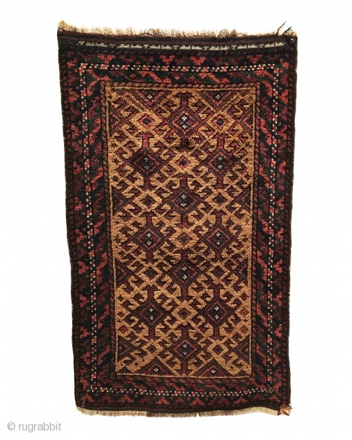 Antique Baluch Small Rug. Late 19th Century. Hooked diamonds float on camel field. Excellent condition. Lower right corner kilim reweave. Full pile. Inscription in white, across top kilim end? 1'6 x 2'6.  ...