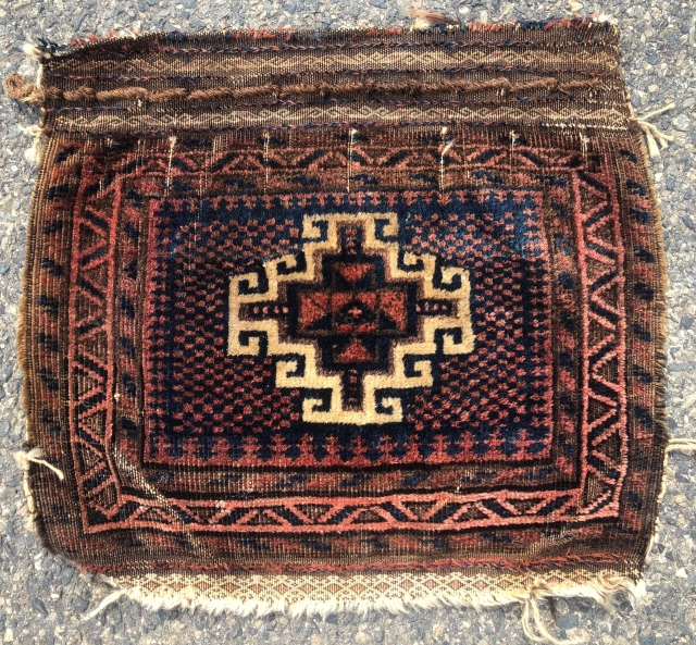 Antique little Baluch bagface with an interesting design feature. The single bold memling gul floats on an unusual checked ground. Overall good even pile. Some brown  oxidation. Creases. Natural colors. Original  ...