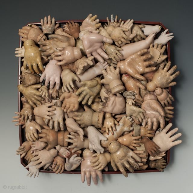 One hundred doll hands of various size on a lacquer stand. Condition varies from pristine hands to those with missing fingers and chipped paint. Europe and USA. Porcelain, composition, paint, wire. Stand  ...