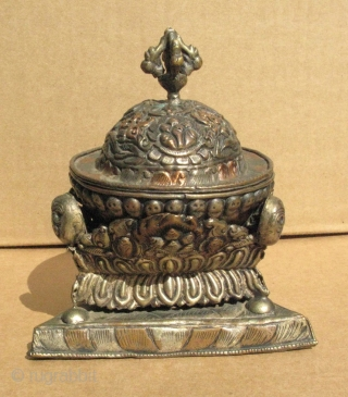 A small vintage Buddhist libations cup, Tibet, made in the form of a Kapala, skull cup, three pieces, the cup, a lid, and a triangular base, silver and copper repousse, decorated with  ...