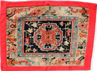 """Antique Tibetan mat or seat cover, first quarter of the 20th century, 23"""" by 30"""", with original edging and backing."""