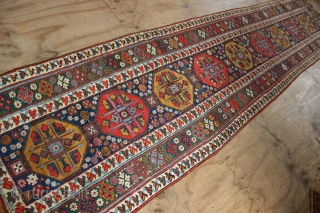 "19th century Kurdish runner with a lovely abrashed emerald green border and regular repeat yellow and red medallions on a midnight blue field. New sidecords applied and minor touches of repiling. 3'2""  ..."