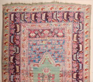 A Colorful Anatolian Prayer Ghordes prayer rug, with a steep triangular gable and a sea-green open field decorated with red carnations along the sides. A dense hyacinth pattern is seen above the  ...