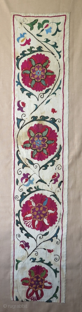 "Antique Suzani fragment. Circa 19th Century. Mounted on cotton fabric. Size: 9.8"" x 50.6""  25 cm x 129 cm."
