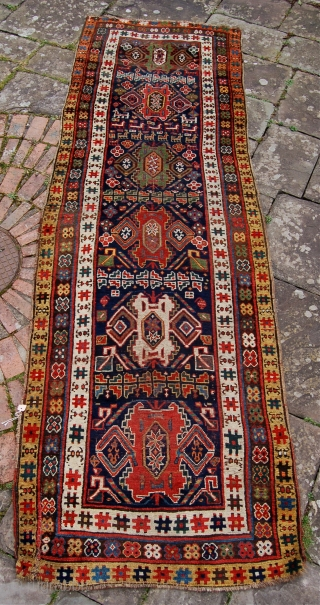 Antique Kurdish carpet. North west Persia. Circa 1850-75. Aprox. 11.5x3.5 ft. Lovely old colours and charming bold graphics. Some low pile and minor damage.