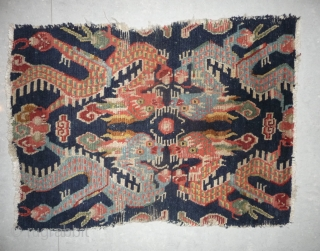 small tibetan mat with a dynamic design made of four edentate dragons. it has been apparently used as saddle top , as the wear on both sides indicates. early 20th, 56x 80cm.