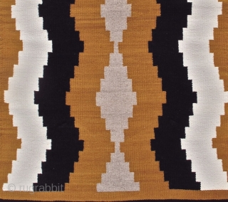 This simple small vintage mid 20th century Navajo rug paints waves of natural ivory and brown to form subtle intimations of side-borders. A column of grey diamonds is drawn along the center  ...