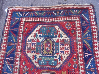 """Colorful Kazak on a red ground with three medallions and several curious figures in the field.  3rd quarter of the 19th century. Size = 4'7"""" x 8'3"""". Inv. # 14692."""