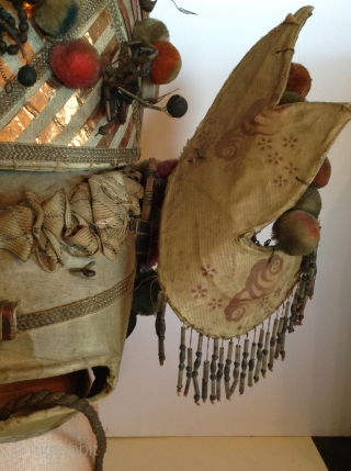 Chinese Theatrical Hat, unique and old.  Made of some kind of stiff, thick material and covered with cloth.  It is decorated with beads, pompons, copper strips, and gold painted pieces.  ...