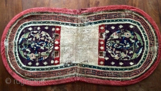 Early Tibetan saddle rug, aubergine ground and amazing Tang style medallions.