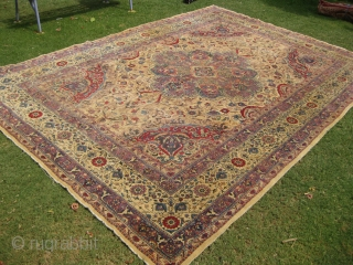 An old Indian rug measuring 14 by 10 feet with scattered wear areas.