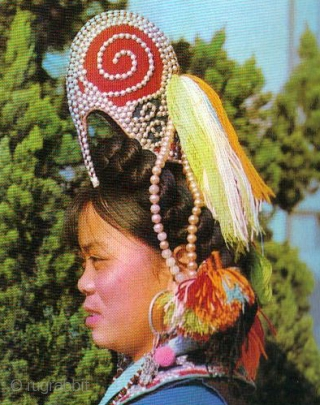 """EMT133  This antique chinese hat would have been worn for festival by a Yi ethnic minority girl (woman) from the Honghe area. Worn for festival, the """"cockssome cap"""" is elaborately decorated  ..."""