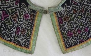 EMT152 This tradition style childs collar of the Chinese Dong Ethnic minority was handmade by the mother or grandmother. The fabric was cut from fragments of handwoven cloth stitched together. The embroidery  ...