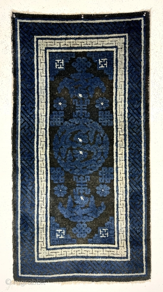 Older Chinese small Baotou rug with interesting dragon design. Look closely and you can see two dragons facing each other. Overall good condition for the age. Indigo pile quite high and black/brown  ...